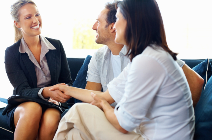Happy couple - mature woman shaking hands with their insurance advisor